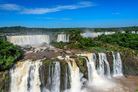 Aerial view of waterfalls cascade of Iguazu Falls with extensive tropical forest and powerful flows of water in Iguacu National Park,   Foz de Iguacu, Parana State, Brazil