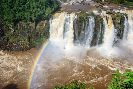 Rainbow and view of cascading water of Iguazu Falls with extensive tropical forest and raging river in Iguacu National Park,   Foz de Iguacu, Parana State, Brazil Reklamní fotografie