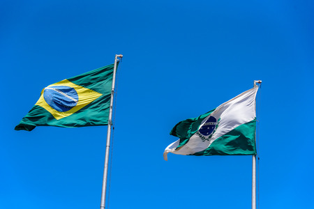 yerba mate: National brazilian flag and flag of Parana waving in the wind at flagpoles on the background of clear blue sky at sunny summer day, Brazil