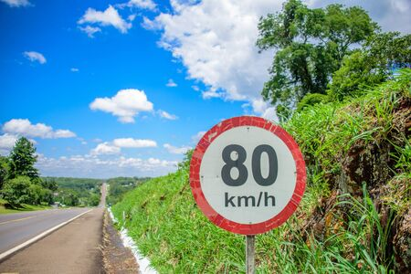 The road sign of 80 kilometres per hour limit on the background of small hill covered with green grass, long road going to horizon and blue sky with white clouds at sunny summer day Reklamní fotografie