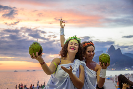 RIO DE JANEIRO, BRAZIL - FEBRUARY 27, 2017: Two women in the costumes of Greek Goddesses wearing flowers diadems and holding coconuts on the background of the beautiful sundown at Ipanema beach Redakční