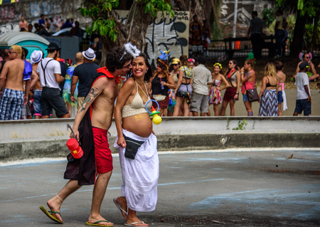 RIO DE JANEIRO, BRAZIL - FEBRUARY 28, 2017: Happy costume husband with hammer and sickle and his pregnant wife with enormous plastic pacifier having fun at Carnaval 2017 Redakční