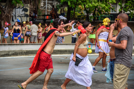 RIO DE JANEIRO, BRAZIL - FEBRUARY 28, 2017: Costume husband with hammer and sickle pretending to bite his happy pregnant wife with enormous plastic pacifier at Carnaval 2017