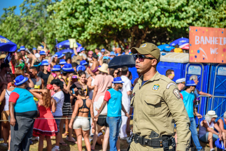 RIO DE JANEIRO, BRAZIL - FEBRUARY 28, 2017: Serious policeman of Municipal Guard in sunglasses working during Bloco Orquestra Voadora on the background of crowd of people, Carnaval 2017 Redakční