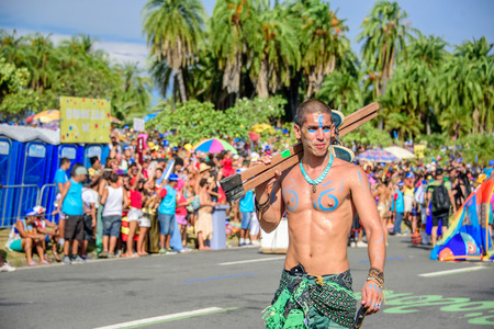RIO DE JANEIRO, BRAZIL - FEBRUARY 28, 2017: One of the artist of Bloco Orquestra Voadora with naked torso carrying his stilts on his shoulder on the background of crowd of people, Carnaval 2017 Redakční