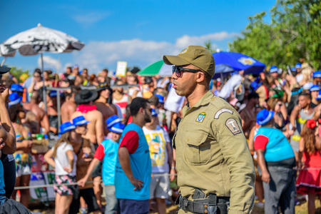 RIO DE JANEIRO, BRAZIL - FEBRUARY 28, 2017: Serious policeman of Municipal Guard in sunglasses working during Bloco Orquestra Voadora on the background of crowd of people, Carnaval 2017 新聞圖片
