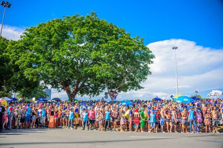 RIO DE JANEIRO, BRAZIL - FEBRUARY 28, 2017: Crowd of costume people in blue sun hats in Flamengo Park waiting for Bloco Orquestra Voadora on the background of blue sky and big trees, Carnaval 2017