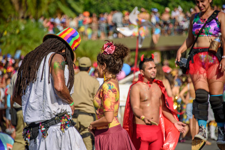 RIO DE JANEIRO, BRAZIL - FEBRUARY 28, 2017: Couple of man with dreadlocks and in colored tall hat and young woman on the background of blurry man in devil costume and woman walking on stilts