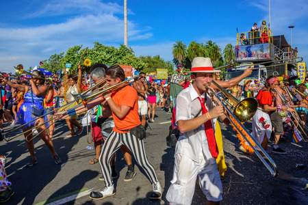 RIO DE JANEIRO, BRAZIL - FEBRUARY 28, 2017: Group of costume musicians playing trombones on the background of platform of Bloco Orquestra Voadora in Flamengo Park, Carnaval 2017