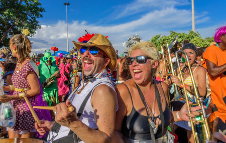 RIO DE JANEIRO, BRAZIL - FEBRUARY 28, 2017: Funny man and woman of Bloco Orquestra Voadora playing drum and trombone, singing and dancing on the background of other musicians, Carnaval 2017