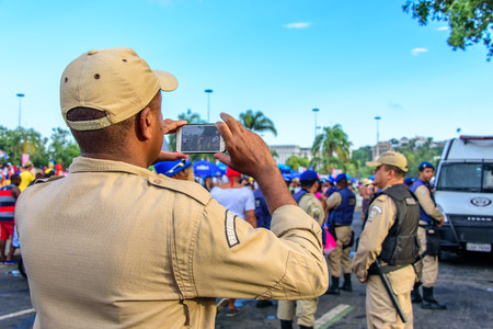 RIO DE JANEIRO, BRAZIL - FEBRUARY 28, 2017: Back of the policeman taking pictures of costume people at Bloco Orquestra Voadora in Flamengo Park on the background of Sugarloaf Mountain, Carnaval 2017 Redakční
