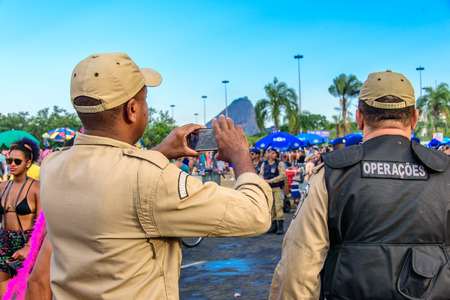 RIO DE JANEIRO, BRAZIL - FEBRUARY 28, 2017: Back of two policemen taking pictures of costume people at Bloco Orquestra Voadora in Flamengo Park on the background of Sugarloaf Mountain, Carnaval 2017