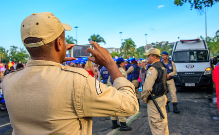 RIO DE JANEIRO, BRAZIL - FEBRUARY 28, 2017: Back of the policeman taking pictures of costume people at Bloco Orquestra Voadora in Flamengo Park on the background of Sugarloaf Mountain, Carnaval 2017 新聞圖片