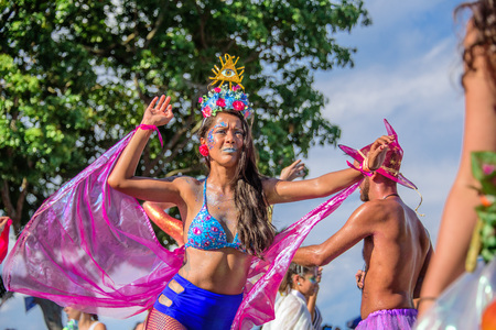 RIO DE JANEIRO, BRAZIL - FEBRUARY 28, 2017: Beautiful woman in bikini with crown of flowers and one-eye symbol on her head walking on stilts during Bloco Orquestra Voadora at Carnaval 2017