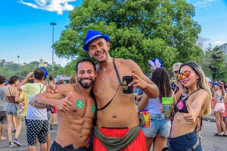 RIO DE JANEIRO, BRAZIL - FEBRUARY 28, 2017: Two men with bare chest and young woman in bikini on the backround of Nossa Senhora da Gloria do Outeiro Church at Bloco Orquestra Voadora, Carnaval 2017