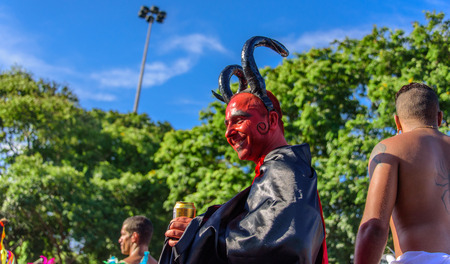 RIO DE JANEIRO, BRAZIL - FEBRUARY 28, 2017: Smiling young man in a costume of devil with red face, big black horns and black and red cloak walking on stilts at Bloco Orquestra Voadora, Carnaval 2017 Editorial