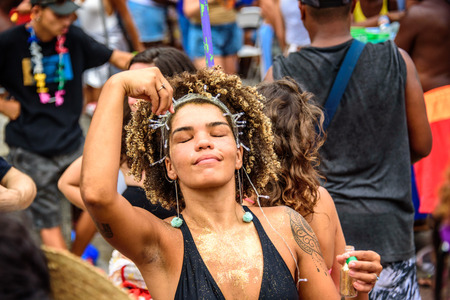 RIO DE JANEIRO, BRAZIL - FEBRUARY 28, 2017: Dreaming beautiful woman with closed eyes, curly hair and fairy-lights on her head, sprinkling golden glitter on herself at Carnaval 2017 新聞圖片