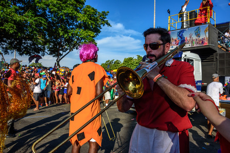 RIO DE JANEIRO, BRAZIL - FEBRUARY 28, 2017: Musician playing trombones on the background of platform of Bloco Orquestra Voadora in Flamengo Park, Carnaval 2017 新聞圖片