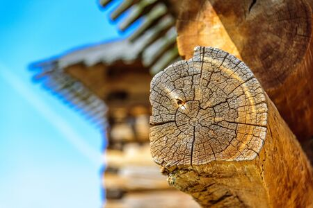 Details of log cabin corner joint with round logs and blurry roof of wooden house on the background at sunny spring day, Moscow, Russia