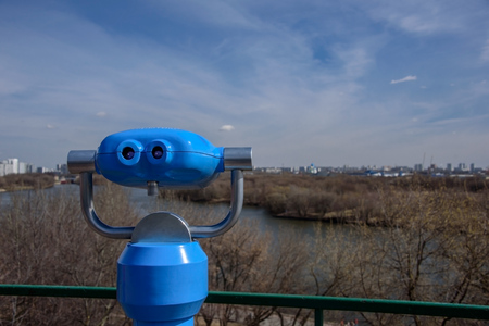 Blue binary telescope of observation deck in park Kolomenskoye, former royal estate, with view of spring forest, Moskva river and the city on the background, Moscow, Russia