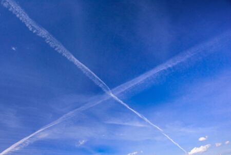 Blue spring sky with X-shaped traces of aircrafts at sunny day