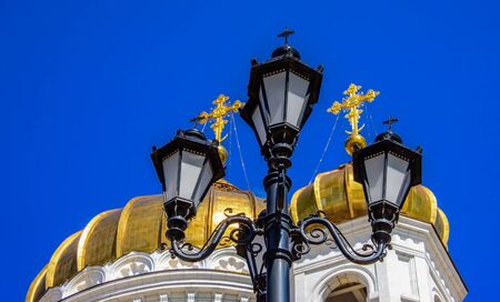 Black carved lantern with crosses on the background of the golden domes of the Russian Orthodox Church and blue monophonic sky