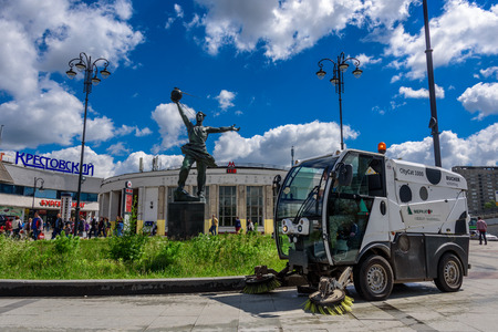 MOSCOW, RUSSIA - JUNE 7, 2017: City cleaning machine, monument to the creators of the first earth satellite, shopping center Krestovsky and entrance to the metro station Rizhskaya at sunny summer day