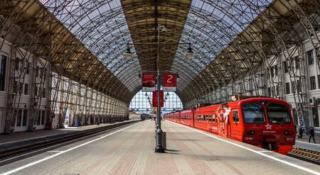 MOSCOW, RUSSIA - MAY 05, 2017: Red Aeroexpress train standing at a gigantic landing platform of Moscow Kiyevskaya railway station and Shukhovs steel-and-glass roof of Kiyevsky station