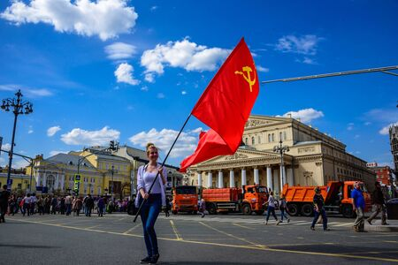 MOSCOW, RUSSIA - MAY 01, 2017: Young woman staying on the background of the Bolshoi Theatre at International Workers Day with a big red flag of the USSR with Hammer and Sickle Redakční