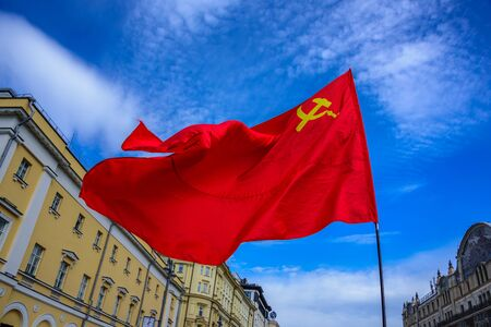 A big red flag of the USSR with Hammer and Sickle waving in the wind on the background of blue sky at International Workers Day