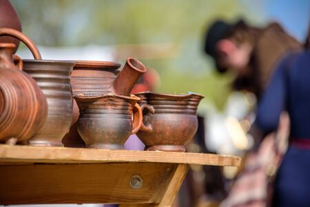 A lot of clay pots standing on a table and blurry man wearing the medieval costume at international knight festival Tournament of Saint George