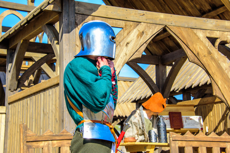 The knight wearing helmet and armor on the background of wooden castle at the international knight festival Tournament of Saint George in the Kolomenskoye museum-reserve