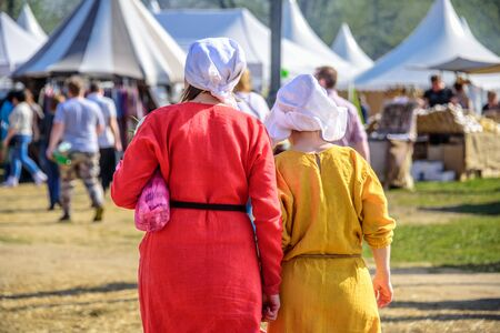 Backs of two young women in the medieval dresses and white kerchiefs walking on the background of tents and people at the international knight festival Reklamní fotografie