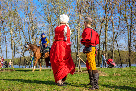 MOSCOW, RUSSIA - APRIL 30, 2017: Woman and man in the medieval costumes talking with horseman at the international knight festival Tournament of Saint George in the Kolomenskoye museum-reserve