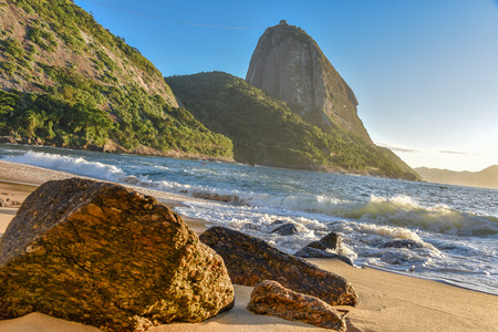 Big stones at the deserted Praia Vermelha Beach and sunrise with the bright sun illuminating the Sugarloaf Mountain at the early morning, Rio de Janeiro, Brazil