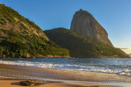 Beautiful sunrise at the deserted Praia Vermelha Beach with the bright sun illuminating the Sugarloaf Mountain at the early morning, Rio de Janeiro, Brazil