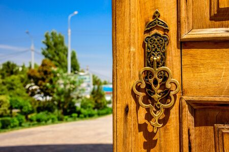 Golden carved handle of the wooden door at sunny summer day in Hazrat Imam Ensemble in the center of Tashkent city, Uzbekistan