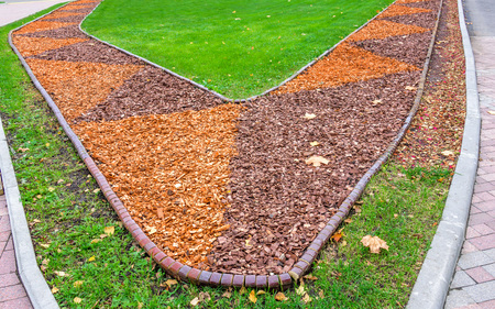 View of colorful orange and brown sawdust in flower bed and green lawn with dry autumn leaves on it