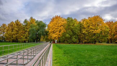 View of colorful alley with bright green and yellow trees, green lawn with dry autumn leaves on it, staircase with handrails and overcast sky in the park at autumn cold day in Moscow city, Russia