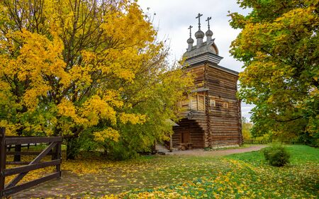 View of beautiful ancient wooden orthodox church circled by yellowed autumn deciduous trees, brown low fence and green lawn with yellow leaves on it at cold November day in the park, Moscow city