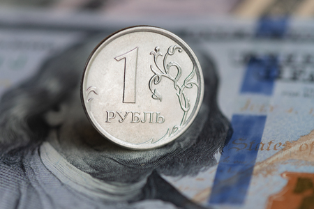 Closeup of one Russian Ruble coin on the background of US dollar banknote
