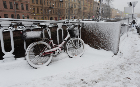 Red bicycle with baskets covered with snow leaning against a fence next to Griboyedov Canal at snowing winter day Reklamní fotografie - 123110220