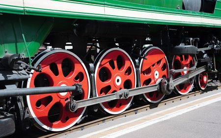 Closeup of four big red driving wheels of a steam locomotive coupled together with side rods on one side of a locomotive and piece of green wagon