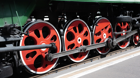 Closeup of four big red driving wheels of a steam locomotive coupled together with side rods on one side of a locomotive at sunny day Reklamní fotografie