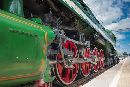 Closeup of four big red driving wheels of a steam locomotive coupled together with side rods, piece of green wagon and railway station platform with blue cloudy sky on the background