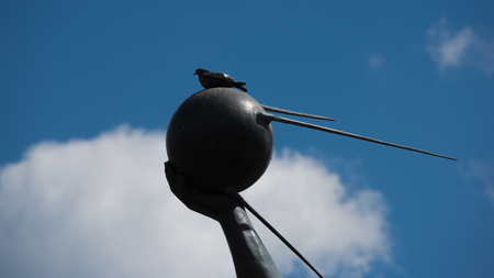 Closeup of hand holding the first artificial earth satellite with dove sitting on it and blue sky with white cloud on the background