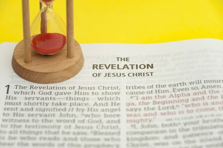 Red sand hourglass on top of open Holy Bible in the Book of Revelation of Jesus Christ chapter 1. Isolated on yellow background. Close-up. Horizontal shot.