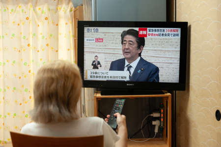 Fuji City, Shizuoka, Japan - May 14, 2020: Coronavirus (COVID-19) Pandemic. A woman watches on Japanese TV [LIVE] Interview by PM Shinzo Abe about canceling