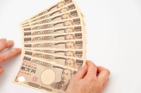 Hands holding 100,000 yen. Isolated on white background. Copy space. Horizontal shot.