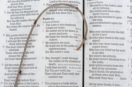 Holy Bible opened in Psalm 23 of David with small wooden staff over the text. Concept: Provision and protection of the Lord in difficult times. Close-up. Horizontal shot.